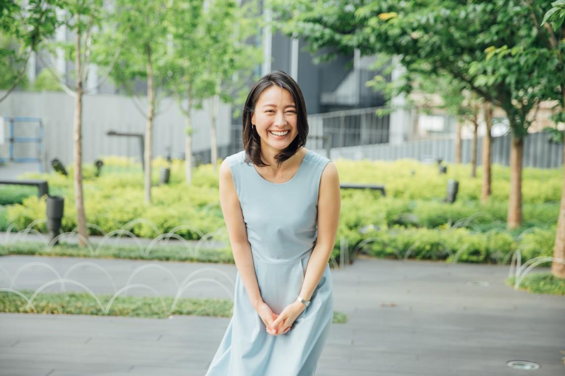 爽やかな青いワンピースを着て緑の多い公園に立つ小川彩佳